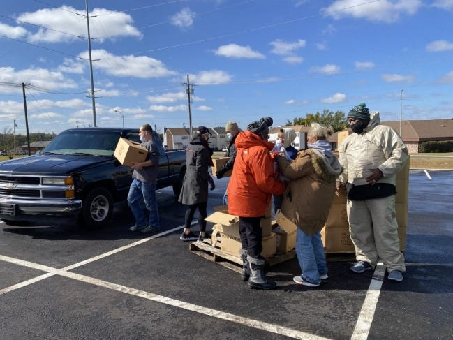 Volunteers and leaders at Ebenezer Baptist Church take food boxes to a resident's vehicle during a drive-thru food distribution at the church, 3600 N Kelley, in partnership with World Vision. [Carla Hinton/The Oklahoman]