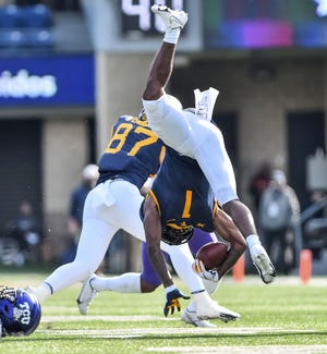 West Virginia wide receiver T.J. Simmons (1) is tackled by TCU safety Ar'Darius Washington (24) during Saturday's game in Morgantown, W.Va. [William Wotring/The Dominion-Post via AP]