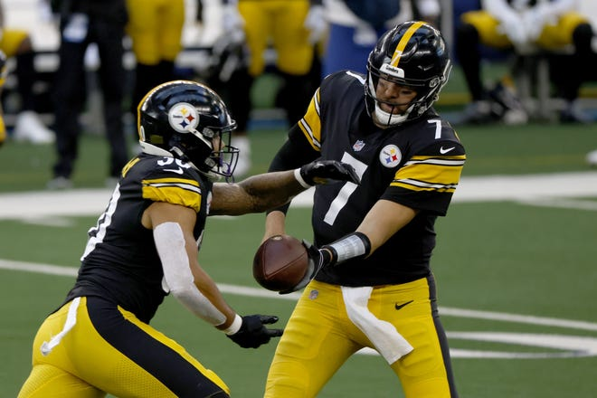 Pittsburgh Steelers running back James Conner (left) takes the handoff from quarterback Ben Roethlisberger in the first half against the Dallas Cowboys. Roethlisberger and three teammates have been removed from the COVID-19 list and will play Sunday against the Bengals. [AP Photo/Ron Jenkins]