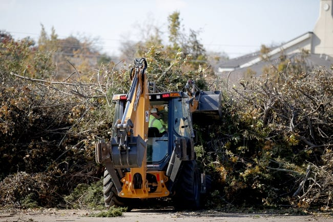 A worker moves tree debris gathered from the 2020 ice storm. The mass of limbs has been converted into mulch that will now benefit surviving trees. [SARAH PHIPPS/THE OKLAHOMAN]