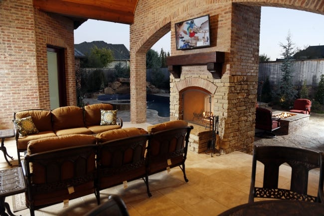 Outdoor living area with a fireplace and fire pit at a home designed by Brent Gibson at 14900 Laurin Lane. [THE OKLAHOMAN ARCHIVES]