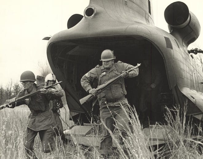 Oklahoma National Guardsmen with the 45th Infantry Division's Third Brigade bound from the back of a CH-47 Chinook helicopter during heavy tactical training in 1966 at Fort Chaffee, Arkansas. Guardsmen from 36 Oklahoma cities and towns were participating in the three-day training exercise. The weekend involved assault airlift training, use of live ammunition, mortar firing testing and communications instruction. This photo was published Nov. 20, 1966, on Page 1 of The Sunday Oklahoman. [GEORGE TAPSCOTT/THE OKLAHOMAN ARCHIVES]