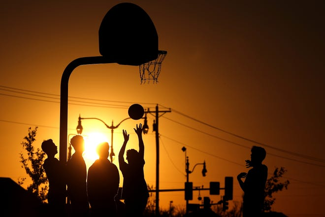 A small group plays basketball at sunset at Edmond's Mitch Park on Monday. Warm temperatures are expected to continue in the metro area until a cold front brings showers and cooler temperatures this weekend. [Bryan Terry/The Oklahoman]