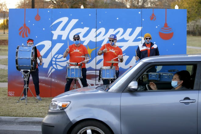 A family drives past the Thunder Drummers during the team's annual Holiday Assist where Thunder staff hosted a Thanksgiving drive-thru event Wednesday to provide Thanksgiving meal kits to children families of the Boys & Girls Club of Oklahoma County. [photos by Bryan Terry/The Oklahoman]
