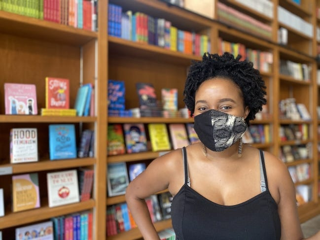 Onikah Asamoa-Caesar stands near book shelves at Fulton Street Books & Coffee, a bookstore she opened in July in Tulsa. [Carla Hinton/The Oklahoman]
