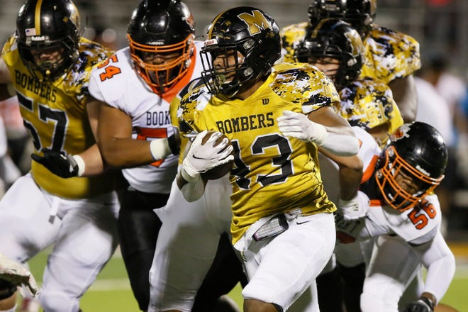 Midwest City's Kristawn Friday carries the ball during a high school football game between Midwest City and Tulsa Washington at Midwest City, Okla., Friday, Nov. 20, 2020. [Bryan Terry/The Oklahoman]