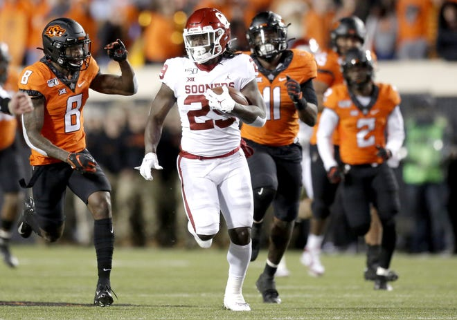 OU's Rhamondre Stevenson (29) rushes away from OSU defenders in the fourth quarter of a 34-16 win last season in Stillwater. [Sarah Phipps/The Oklahoman]