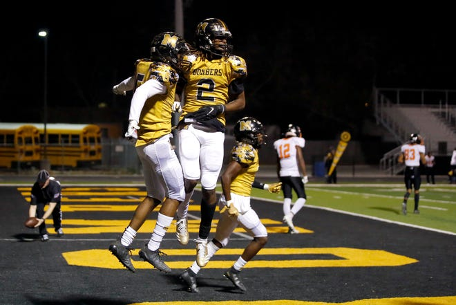 Midwest City's Makale Smith (2) and Brian Wilson Jr. of Midwest City celebrate after Wilson Jr. intercepted a pass during a high school football game between Midwest City and Tulsa Washington at Midwest City, Okla., Friday, Nov. 20, 2020. [Bryan Terry/The Oklahoman]