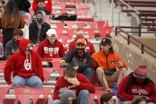 Oklahoma and Oklahoma State fans, many wearing masks and practicing social distancing, find their seats Saturday before the Bedlam college football game between the OU Sooners and the OSU Cowboys at Gaylord Family-Oklahoma Memorial Stadium in Norman. See full coverage of the late-playing game online at Oklahoman.com. [Bryan Terry/The Oklahoman]