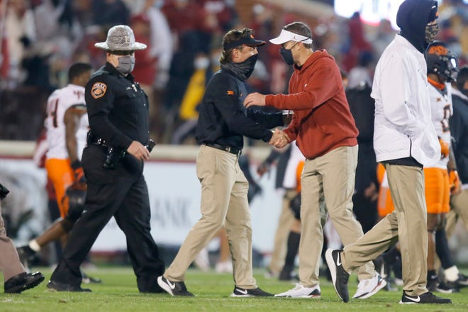 Oklahoma coach Lincoln Riley, right, greets Oklahoma State coach Mike Gundy after a bedlam college football game between the University of Oklahoma Sooners (OU) and the Oklahoma State Cowboys (OSU) at Gaylord Family-Oklahoma Memorial Stadium in Norman, Okla., Saturday, Nov. 21, 2020. Oklahoma won 41-13. [Bryan Terry/The Oklahoman]