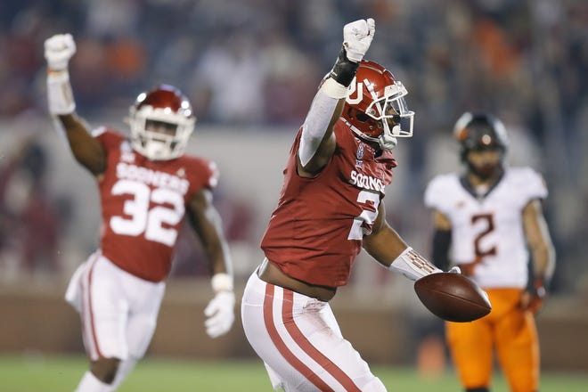 Oklahoma's David Ugwoegbu, middle, celebrates after an interception during Saturday's Bedlam football game in Norman. Oklahoma beat Oklahoma State 41-13. Coverage of the game begins in Sports on page B1. [Bryan Terry/The Oklahoman]