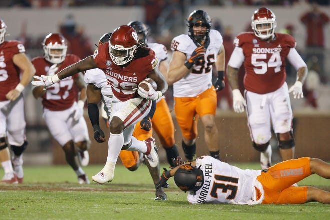 OU's Rhamondre Stevenson (29) leaps over OSU's Kolby Harvell-Peel (31) en route to a 141-yard rushing day in a 41-13 win Saturday night in Norman. [Bryan Terry/The Oklahoman]