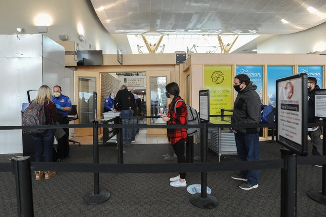 Travelers head through a Transportation Security Administration checkpoint at the Idaho Falls Regional Airport on Tuesday, Nov. 24, 2020. (John Roark/The Idaho Post-Register via AP)
