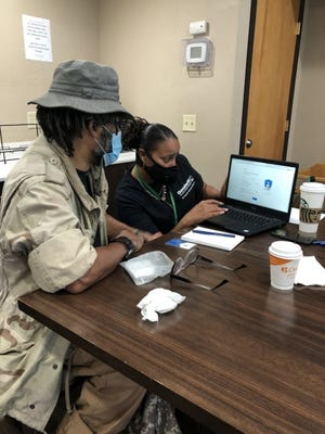 An employee at Goodwill Industries helps a veteran search for services. [Photo provided]