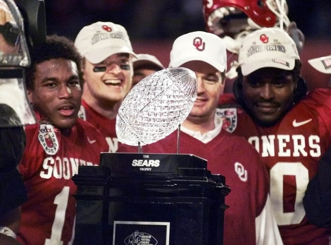 OU linebacker Torrance Marshall (right) stares at the national championship trophy with coach Bob Stoops (center) and quarterback Josh Heupel (second from left) after the Sooners beat Florida State 13-2 in the Orange Bowl on Jan. 3, 2001, in Miami. [STEVE SISNEY/THE OKLAHOMAN]