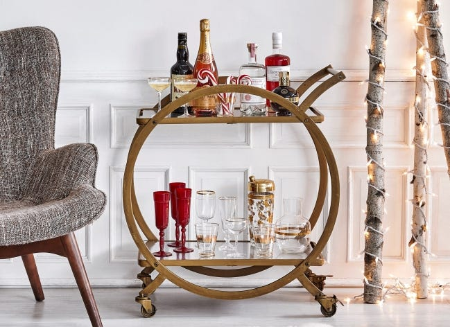 Tiny white Christmas lights wrapped around birch branches add a festive feel to this holiday drink cart. [PHOTO PROVIDED/ANTONIS ACHILLEOS]