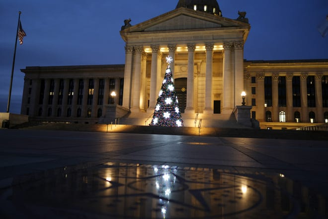 The Christmas Tree on the south steps of the Capitol is reflected in the granite Seal of Oklahoma in the South Plaza on Monday.  [Doug Hoke photos/The Oklahoman]