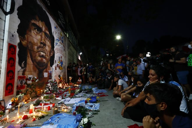 Soccer fans hold a vigil for Diego Maradona outside the stadium of Argentinos Juniors soccer club, where he started as a professional footballer, in Buenos Aires, Argentina. The Argentine soccer great who was among the best players ever and who led his country to the 1986 World Cup title died from a heart attack at his home in Buenos Aires. He was 60. [AP Photo/Marcos Brindicci]