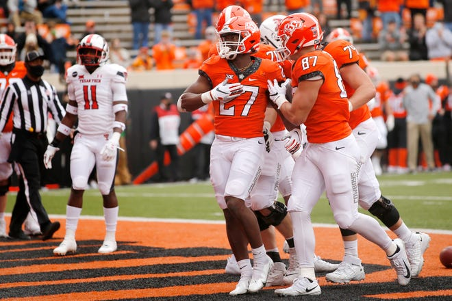 Nov 28, 2020; Oklahoma State Cowboys running back Dezmon Jackson (27) celebrates beside tight end Logan Carter (87) after running for a touchdown during a football game against Texas Tech in Stillwater, Oklahoma, USA; at Boone Pickens Stadium. Mandatory Credit: Bryan Terry-USA TODAY Sports