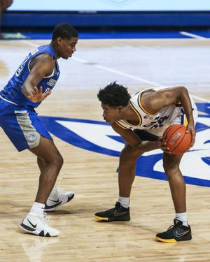 Louisiana State guard Cam Thomas, right, holds onto the ball while looking to pass as Saint Louis guard Demarius Jacobs (15) defends Saturday. [Cheyenne Boone/St. Louis Post-Dispatch via AP]