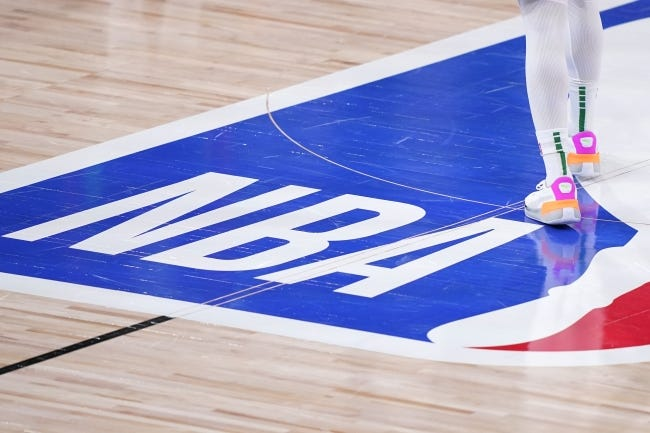 A player walks over the NBA logo on the court during the first half of a Celtics-Heat playoff game last Sept. 25 in Lake Buena Vista, Fla. [AP Photo/Mark J. Terrill]