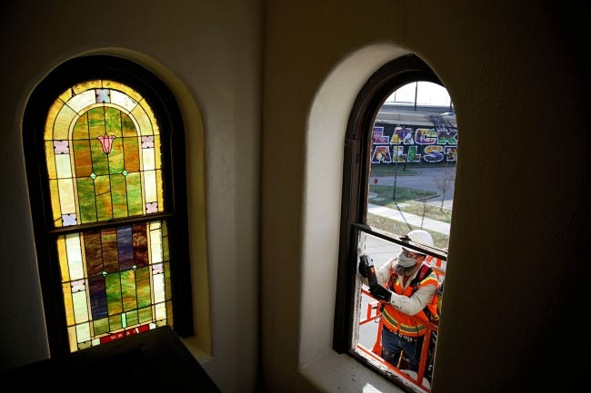 Ron Rayer works to remove stained glass windows on Tuesday at Vernon African Methodist Episcopal Church in Tulsa. [Tulsa World]