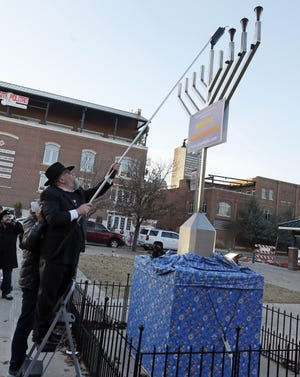 Rabbi Ovadia Goldman lights a giant menorah during the 2016 Bricktown Hanukkah event hosted by Chabad Community Center for Jewish Life & Learning at Third Base Plaza outside Chickasaw Bricktown Ballpark. [The Oklahoman Archives]