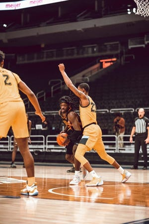 Oklahoma State's Isaac Likekele, middle, dribbles against Marquette on Tuesday. [Courtney Bay/OSU Athletics]