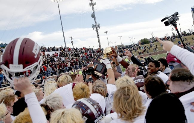 Jenks celebrates with the gold ball trophy after beating Edmond Santa Fe 41-14 for the Class 6A-I state championship Saturday at Wantland Stadium in Edmond. [Sarah Phipps/The Oklahoman]