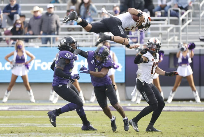 Oklahoma State quarterback Spencer Sanders (3) is hit and flipped in the air by TCU cornerback Tre'Vius Hodges-Tomlinson (1) as OSU receiver Dillon Stoner (17) and TCU defensive end Ochaun Mathis (32) look on during the second half of the Horned Frogs' 29-22 win Saturday in Fort Worth, Texas. [AP Photo/Ron Jenkins]