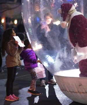 A girl holds up a printed list Saturday for Santa in the Globe to read during Automobile Alley's Lights on Broadway. [Doug Hoke/The Oklahoman]