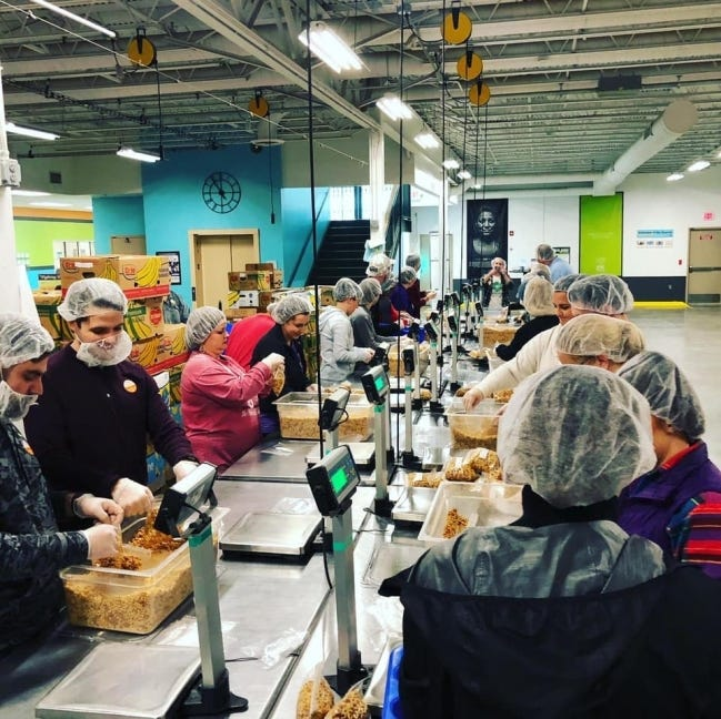 Addison Group employees pack food during their yearly volunteer trip to the Regional Foodbank. [SUBMITTED PHOTO]