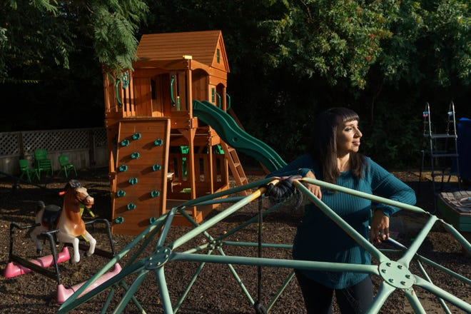 Mary De La Rosa stands inside a play structure in her home backyard, that once housed the now-closed child care program, Creative Explorers, Oct. 21 in Los Angeles. [Damian Dovarganes/the associated press]