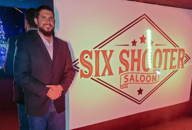 Six Shooter Saloon owner Adam Lawson stands for a photo on the stage at his bar in Oklahoma City on Saturday night. The bar enjoyed some extended hours of business Saturday night when Lawson decided to stay open past the statewide 11 p.m. curfew amid an ongoing legal battle. [David Dishman/The Oklahoman]