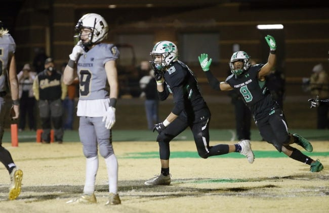 Cole Limber (center) and Adam Wheeler (right) of Bishop McGuinness celebrate after Limber caught a touchdown pass to put the Irish ahead in the final seconds of a high school football playoff game against McAlester in Oklahoma City on Friday. [Bryan Terry/The Oklahoman]