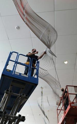 "Fabricator Kevin Maag installs the artwork ""Virga"" in the Bennett Events Center at the OKC Fairgrounds on Tuesday. [Doug Hoke/The Oklahoman]"