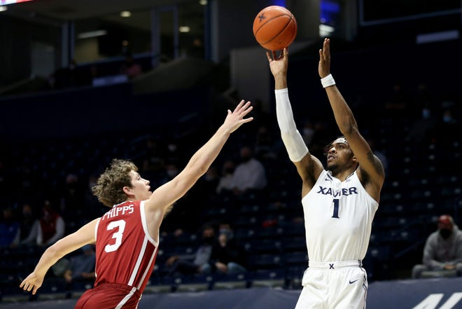 Xavier Musketeers guard Paul Scruggs (1) shoots a fadeaway jump shot as Oklahoma Sooners guard Trey Phipps (3) defends in the first half of a men's NCAA college basketball game, Wednesday, Dec. 9, 2020, at Cintas Center in Cincinnati.  Oklahoma Sooners At Xavier Musketeers Dec 9