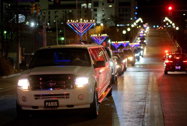 """The """"Procession of Light"""" coordinated by the Chabad Community Center for Jewish Life and Learning heads south over the Walnut Street bridge on Thursday in Bricktown, in celebration of the first night of Hanukkah.  [Doug Hoke/The Oklahoman]"""