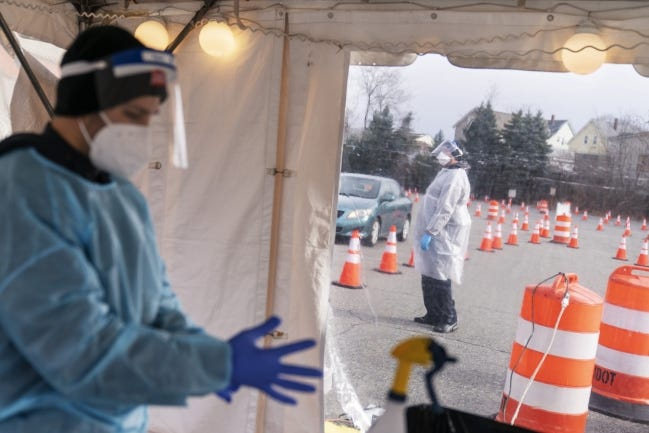 Health care workers prepare to test motorists for COVID-19 at a testing site in Rhode Island. [AP Photo]
