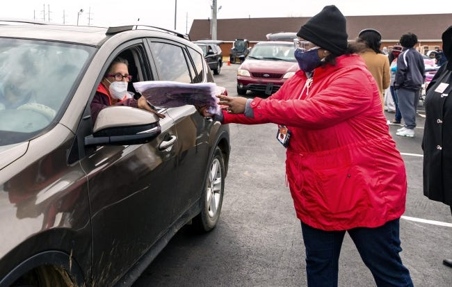 """A volunteer hands an item to Shawna Keith as she drives through the line to receive food boxes and other essentials during the """"Simultaneous Free Food Box Giveaway"""" on Friday at Ebenezer Baptist Church in Oklahoma City. [Chris Landsberger/The Oklahoman]"""