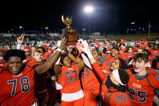 Carl Albert celebrates with the Class 5A state title trophy after beating McGuinness on Saturday at the University of Central Oklahoma's Wantland Stadium in Edmond. [Bryan Terry/The Oklahoman]