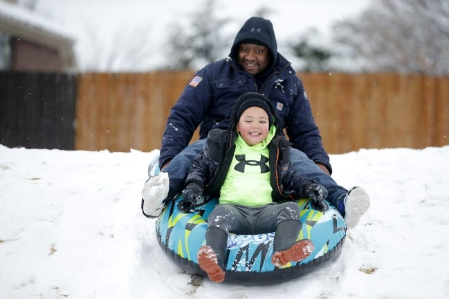 Jack Dumas and his son Layton Dumas, 5, slide down a snow-covered hill Sunday after a winter storm in Oklahoma City. [Bryan Terry/The Oklahoman]