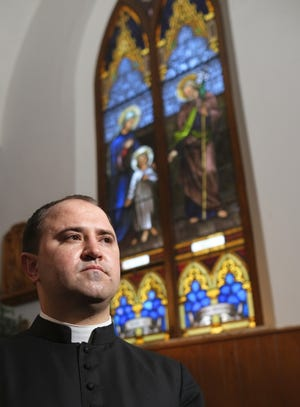 The Rev. Cory Stanley, pastor of Holy Trinity Catholic Church, stands in the sanctuary of the Okarche house of worship. [Doug Hoke/The Oklahoman]