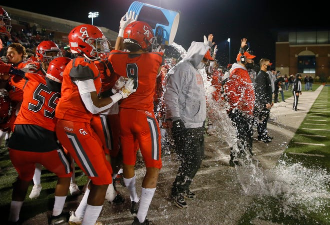 Carl Albert players douse coach Mike Corley during a Class 5A high school football championship game between Carl Albert and Bishop McGuinness at Wantland Stadium in Edmond, Okla., Saturday, Dec. 12, 2020. [Bryan Terry/The Oklahoman]