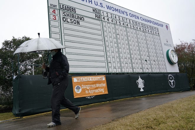 A person carries an umbrella while walking next to a sign advising that play is temporarily suspended during a weather delay in the final round of the U.S. Women's Open in Houston. [AP Photo/David J. Phillip]
