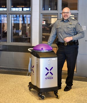 Cleveland County Sheriff Chris Amason poses with Deputy Germinator at the Cleveland County Detention Center. The robot, bought from XENEX, zaps disease-causing pathogens, including those that cause COVID-19. [PHOTO PROVIDED]