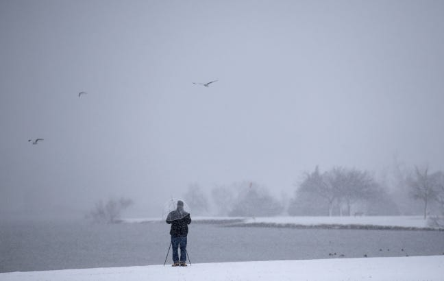 A person takes photographs at Lake Hefner during Tuesday's snow shower in Oklahoma City. [Sarah Phipps/The Oklahoman]