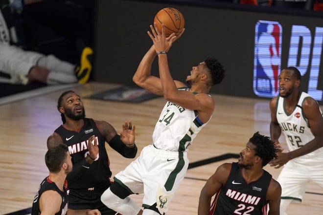 Miami Heat's Goran Dragic, bottom left, Jae Crowder, top left, and Jimmy Butler (22) defend as Milwaukee Bucks' Giannis Antetokounmpo (34) shoots during the first half of an NBA conference semifinal playoff game in Lake Buena Vista, Fla., on Monday, Aug. 31. Having the NBA's best regular-season record and the league's MVP each of the last two years hasn't paid off for the Bucks in the playoffs. They're hoping an offseason overhaul of their roster will help them earn the title that has eluded this franchise since 1971 and make sure two-time reigning MVP Giannis Antetokounmpo stays in Milwaukee for years to come. [AP Photo/Mark J. Terrill, File]