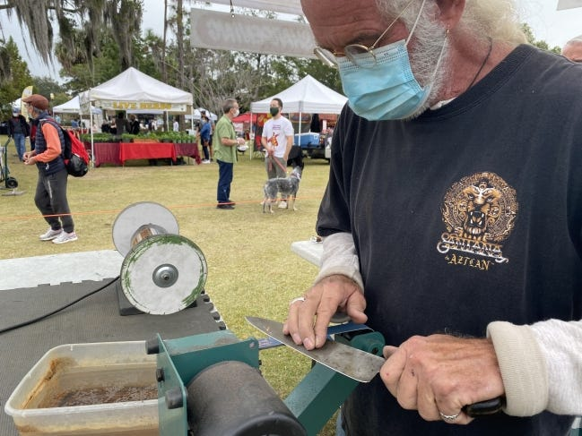 Gregg Kurtz, owner of Chef's Edge, sharpens knives for customers every weekend at the Winter Park and Mt. Dora Farmers Markets in Florida. [MARNI JAMESON]