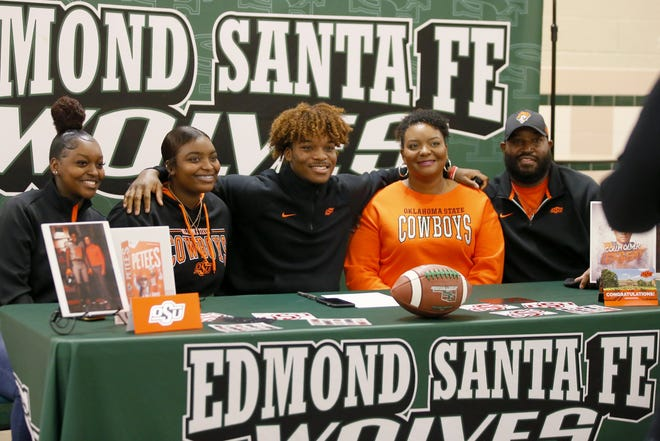 Collin Oliver of Edmond Santa Fe poses for a photo with his sisters Alexis, left, and Mikaylah, second from left, along with his mother, Jewell, and father, Marshall, after announcing he is going to Oklahoma State Univeristy during an early signing day ceremony Wednesday in Edmond. [Bryan Terry/The Oklahoman] Oklahoma high school football players sign their letters of intent as early signing day begins, minus the usual fanfare due to the coronavirus pandemic. Coverage on Pages B1-B5.